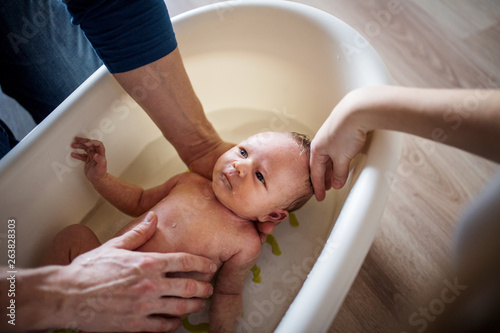 Unrecognizable parents giving a newborn baby a bath at home. Fototapeta