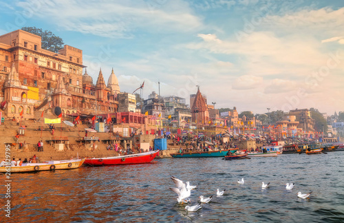 Canvas Prints Old building Varanasi Ganges river ghat with ancient city architecture with view of migratory birds on river Ganga at sunset.