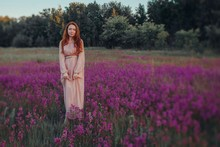 Pretty Redhead Girl Wearing Long Beautiful Gown Standing At Summer Field With Violet Flowers