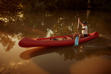 Man Paddling Red Canoe In The River.