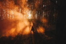 Silhouette Of Girl Walking By Fog In Sunset Light In Pine Forest