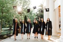 Female Graduates Tossing Caps ...