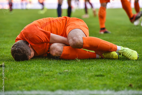 Fotografie, Obraz The injured footballer lies on the pitch.