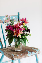 Bright Bouquet Of Late Summer Flowers In A Vase On A Weathered, Antique Chair