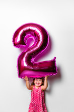 Baby Girl Holding A Number 2 Balloon For Her Birthday