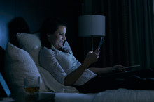 Business: Checking Texts While Watching TV In Bed