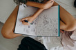 Anonymous young female model woke up and drawing in her sketch book in bed