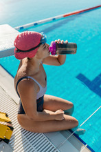Woman Swimmer Drinking From A Bottle