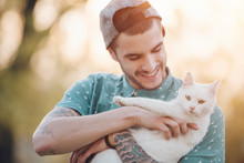 Young Man Holding A White Cat