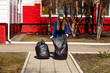 thirty-year-old woman collects garbage in large plastic bags . Care of the environment, cleaning of the territory, waste disposal