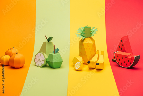 various handmade paper fruits on stripes of colorful paper