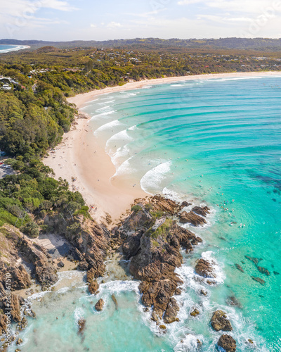 Fotografering Aerial shot at sunrise over the ocean and white sand beach with swimmers and sur