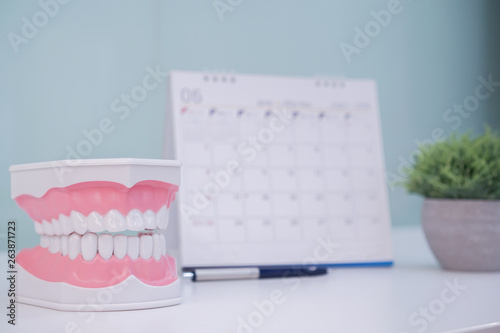 Photo close up on dental tooth denture with calendar on dentist office table for appoi
