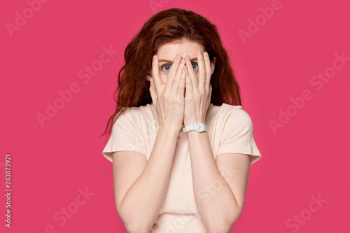 Scared redhead girl cover face peeking through fingers Wallpaper Mural