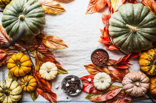Autumn food background with colorful pumpkins , chocolate, spices, nuts and autumn leaves, top view. Autumn still life with pumpkins. Thanksgiving or Halloween recipes. Flat lay. Seasonal cooking