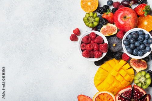 Healthy raw rainbow fruits, mango papaya strawberries oranges passion fruits berries on oval serving plate on light kitchen top, top view, copy space, selective focus - 263883163