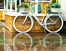 White Vintage Bicycle With Floral Baskets Standing Outside At Cafe Background. Retro Style Transport With Beautiful Flowers