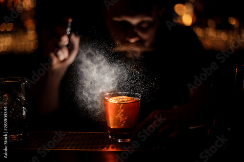 Darkened picture of bartender pours an alcohol cocktail using sprayer