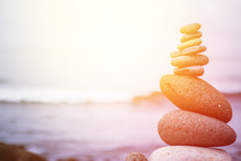 Balance, Relaxation And Wellness: Stone Cairn Outside, Ocean In The Blurry Background. Sunshine.