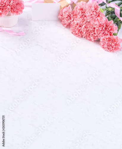 Fototapeta Design concept - Beautiful bunch of carnations on marble white background, top view, copy space, close up, mock up. Mothers day gift idea inspiration. obraz na płótnie