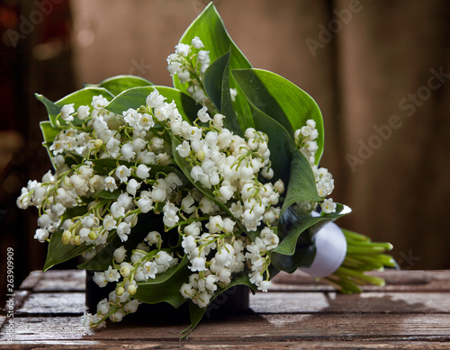 Wall Murals Bouquet of lily of the valley on the brown background