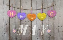Hello May Written On Hanging Pink And Orange And Purple Hearts And Weathered Wooden Background, With Flowers