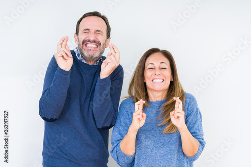 Beautiful middle age couple in love over isolated background smiling crossing fingers with hope and eyes closed Fototapete