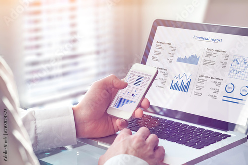 Accountant working on consolidated financial report of corporate operations, consultant auditing finance data (balance sheet, income statement) on screen with business charts, fintech, manager
