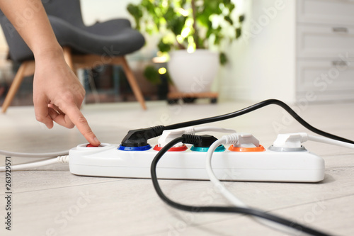 Pinturas sobre lienzo  Woman pressing power button of extension cord on floor indoors, closeup