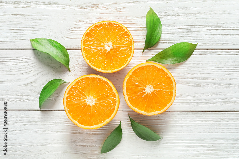 Fototapeta Fresh oranges with leaves on wooden background, flat lay