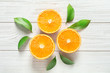 Fresh oranges with leaves on wooden background, flat lay
