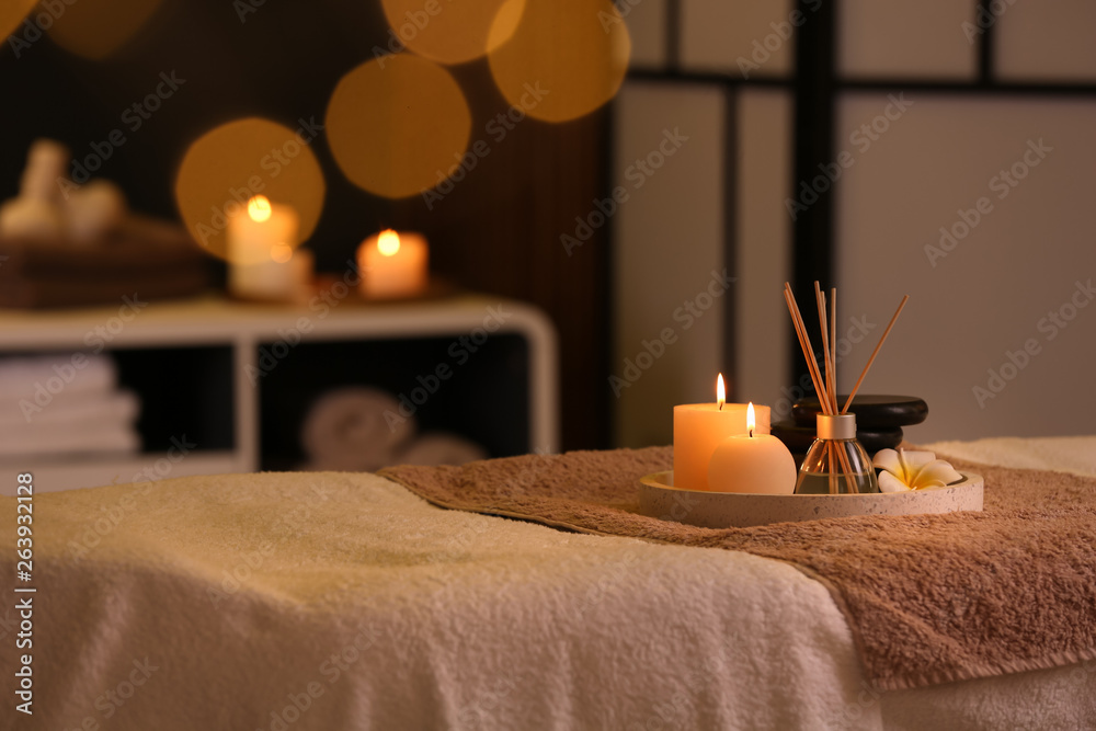 Fototapeta Burning candles and aromatic reed freshener on table in spa salon, space for text