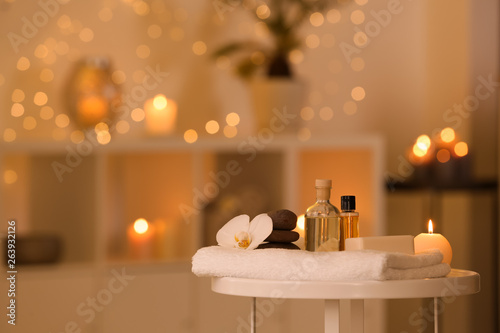 Spa supplies, burning candle and flower on table in beauty salon, space for text