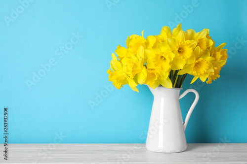 Canvas Print Bouquet of daffodils in jug on table against color background, space for text