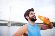 Take A Break.Handsome Fitness Man Holding Water Bottle