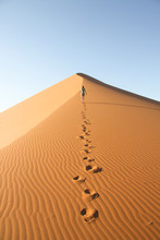 Person Leaving Footprints On Sand Dune