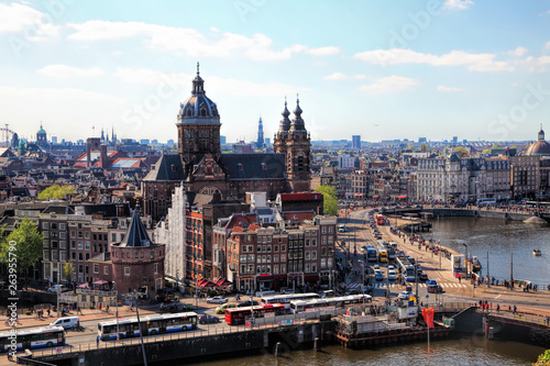 Aluminium Prints Amsterdam Amsterdam cityscape with Grand Amarath hotel. City streets with active tram and car traffic along the canal. Panoramic distance view.