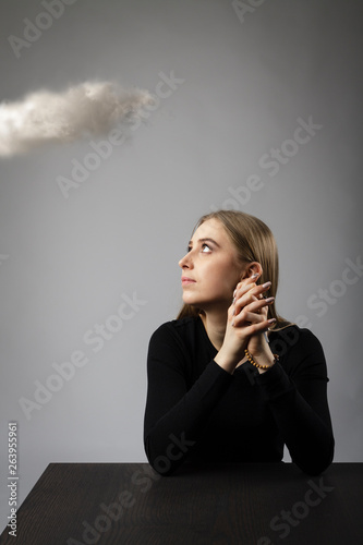 Young woman is praying with rosary beads and cloud. Wallpaper Mural