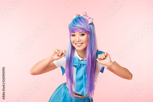 Obraz na plátně Smiling asian anime girl in wig posing isolated on pink