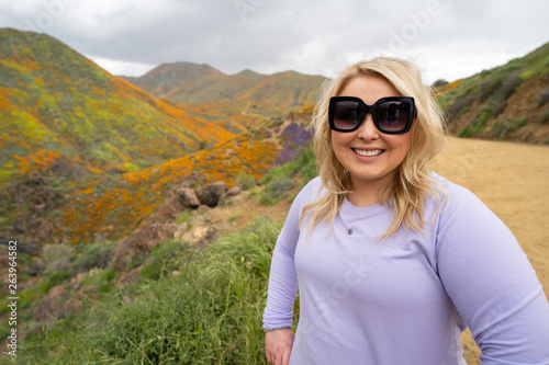 Fotografija  Cute blond woman wearing sunglasses and casual clothing poses at Walker Canyon w