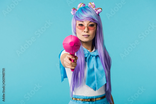 Serious asian anime girl in wig and glasses holding water gun isolated on blue Wallpaper Mural
