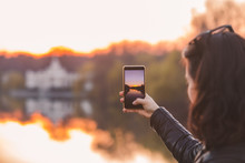 Woman Taking Picture Of Sunset On Her Phone