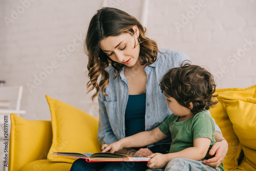 Photo Mom and son sitting on yellow sofa and reading book