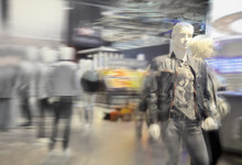 Department Store Blur Photo Background. Shopping Mall Defocused Photo For Banner Template Or Backdrop. Sale Season Blurry Image. Clothes Retail Mannequins.
