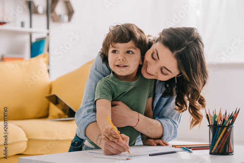 Photo Mother and son drawing with color pencils in living room