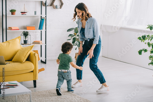 Photo Full length view of smiling woman with son in living room
