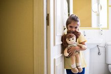 Portrait Of Smiling Little Girl Standing In Doorframe At Home Holding A Doll
