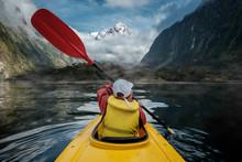Young Boy In Bright Yellow Kayak On Mountain Lake. White Mountain Peak In The Background