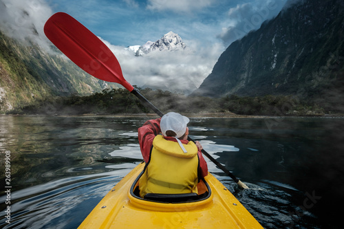 Fotografija Young boy in bright yellow kayak on mountain lake