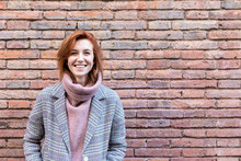Portrait Of A Happy Young Woman Standing At A Brick Wall